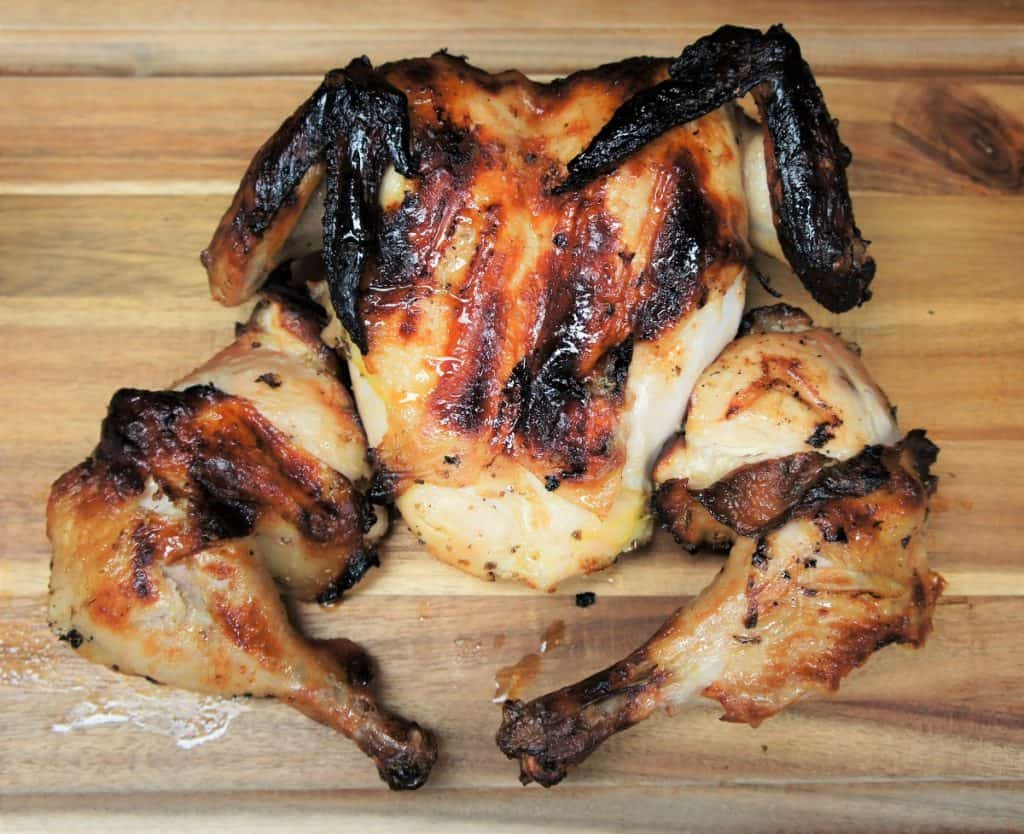 A whole grilled chicken that was marinaded for 24 Hours in a mojo marinade displayed on a wood cutting board