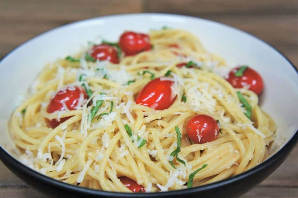 A close up picture of spaghetti aglio e olio with fresh tomatoes and basil served in a white bowl.