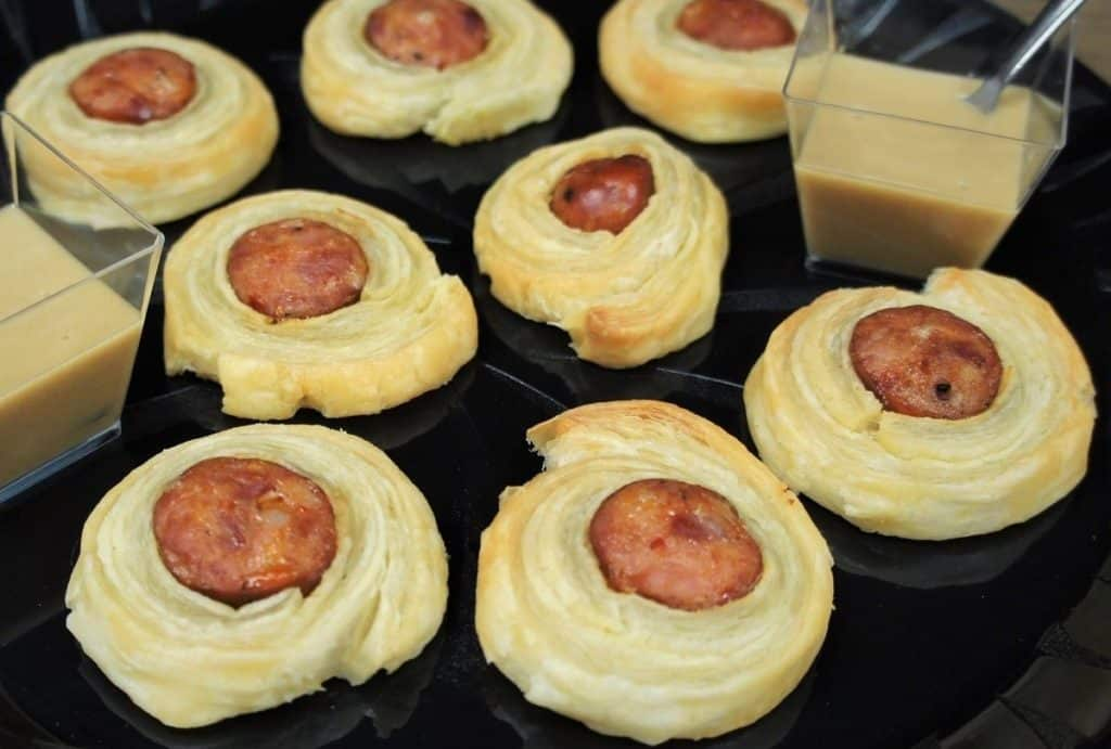 Andouille Sausage Puffs sliced sausage wrapped in puff pastry arranged on a black platter and served with a mustard sauce on the side