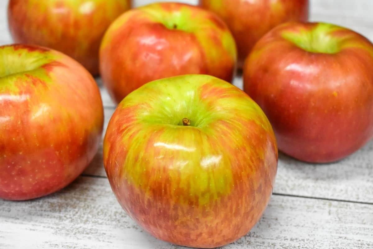 Several honeycrisp apples arranged on a white table.