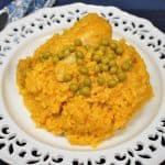 Cuban arroz con pollo, yellow rice with a chicken drumstick served on a white plate and garnished with sweet peas.