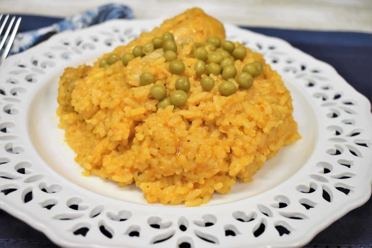 A close up picture of arroz con pollo, garnished with sweet peas and served on a white plate.