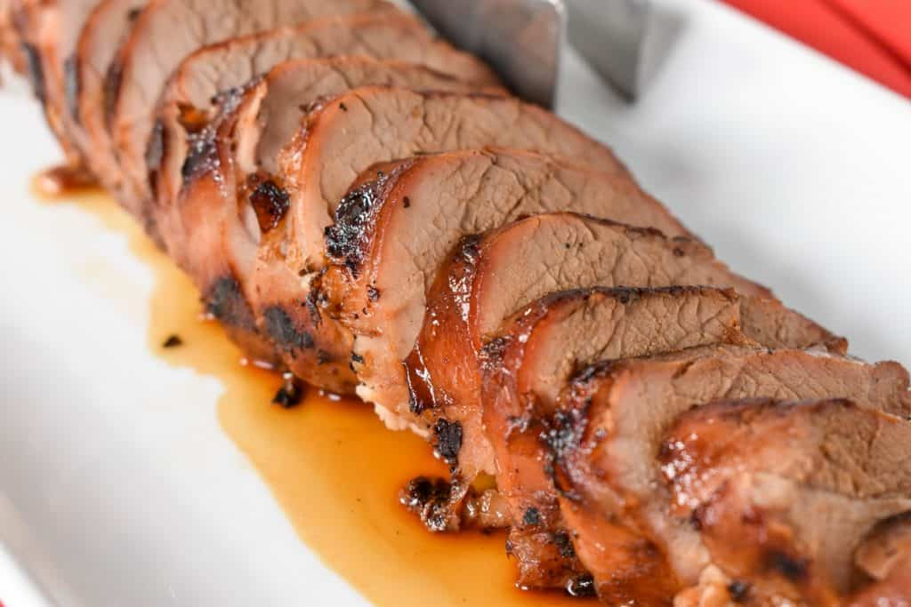Asian marinated pork tenderloin sliced into thin pieces and served on a white platter.