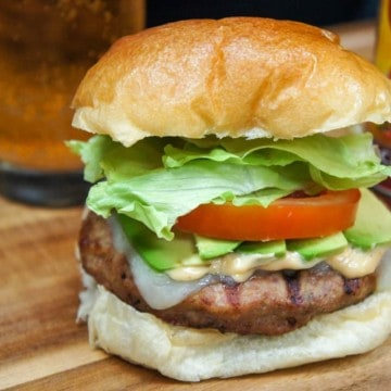 A burger stack high with avocado, tomato and lettuce on a wood cutting board with a beer glass and hot sauce in the background.