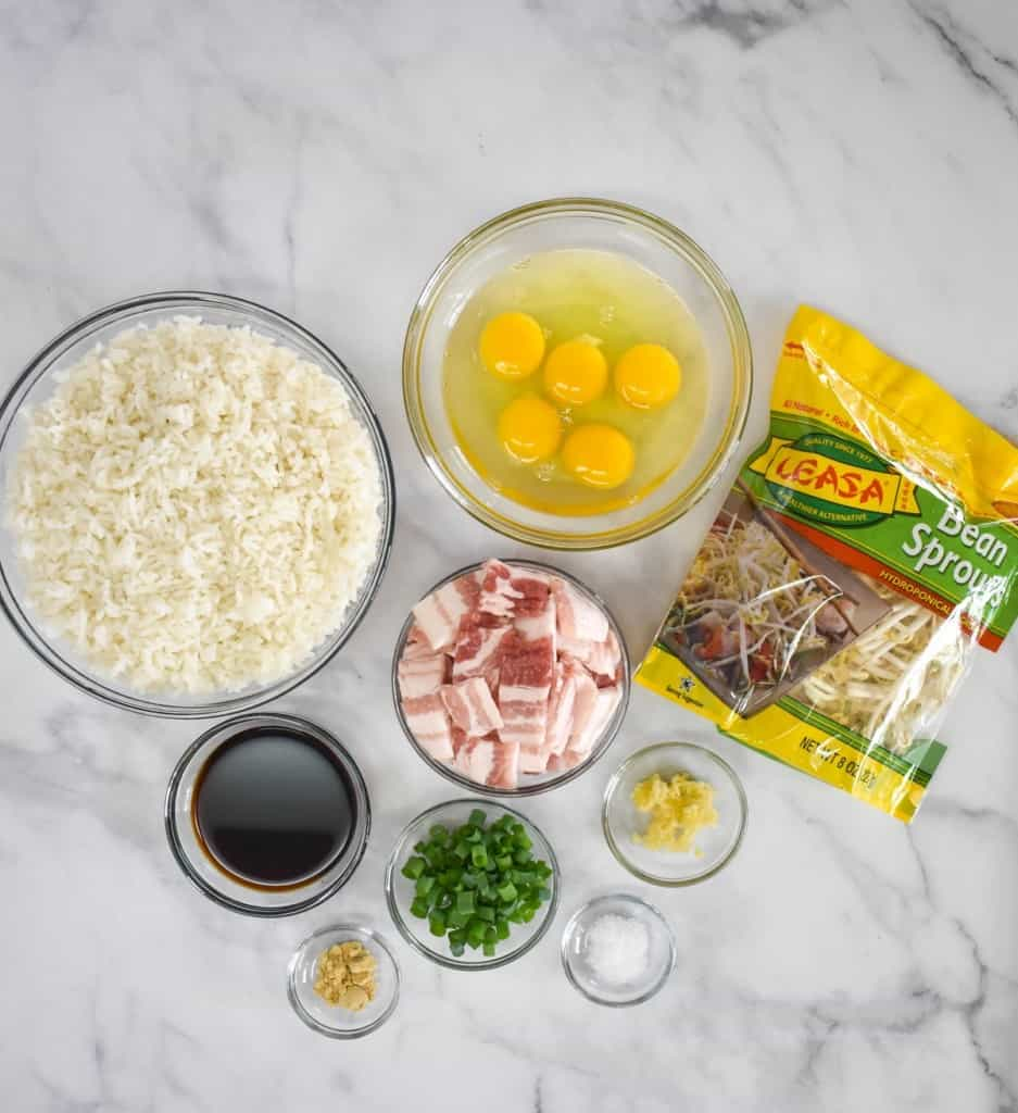 The prepped ingredients for the bacon fried rice arranged on a white table.
