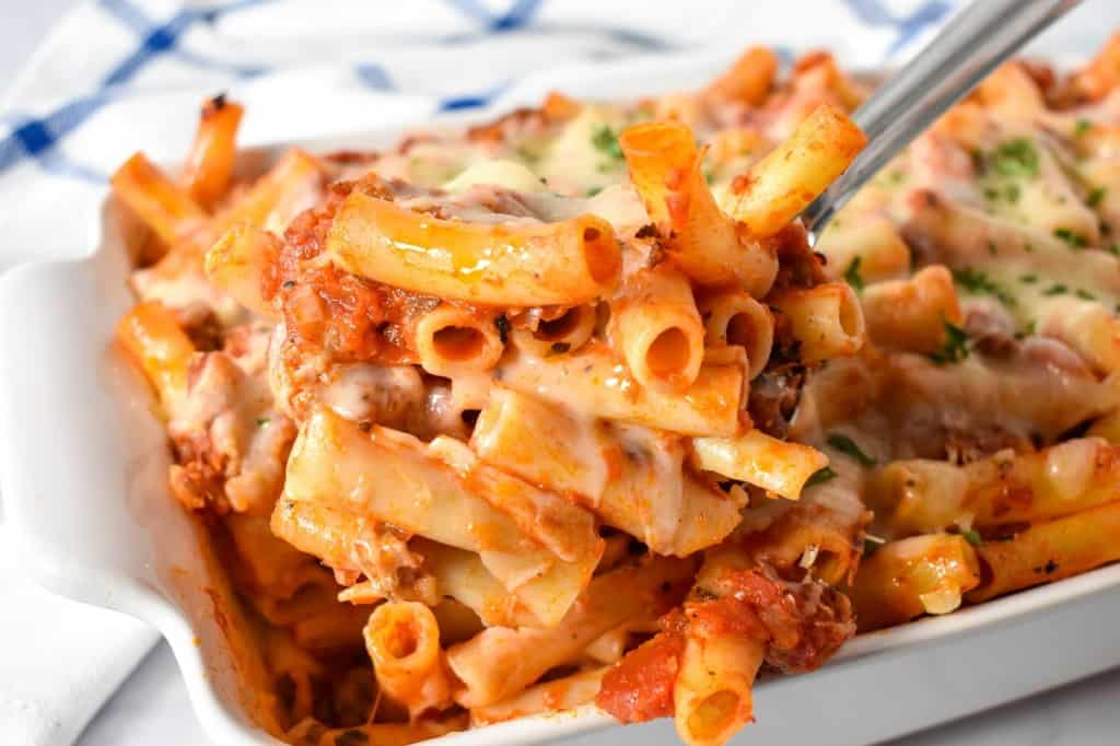 The a serving spoon holding up a serving of the baked ziti.