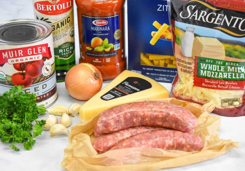 The ingredients for the baked ziti arranged on a white table.