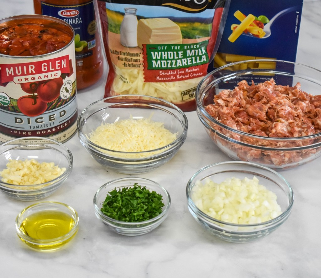 The prepped ingredients for the baked ziti with sausage arranged on a white table.