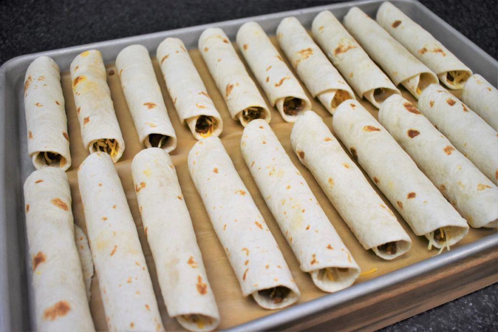 Beef Taquitos arranged on a Baking Sheet