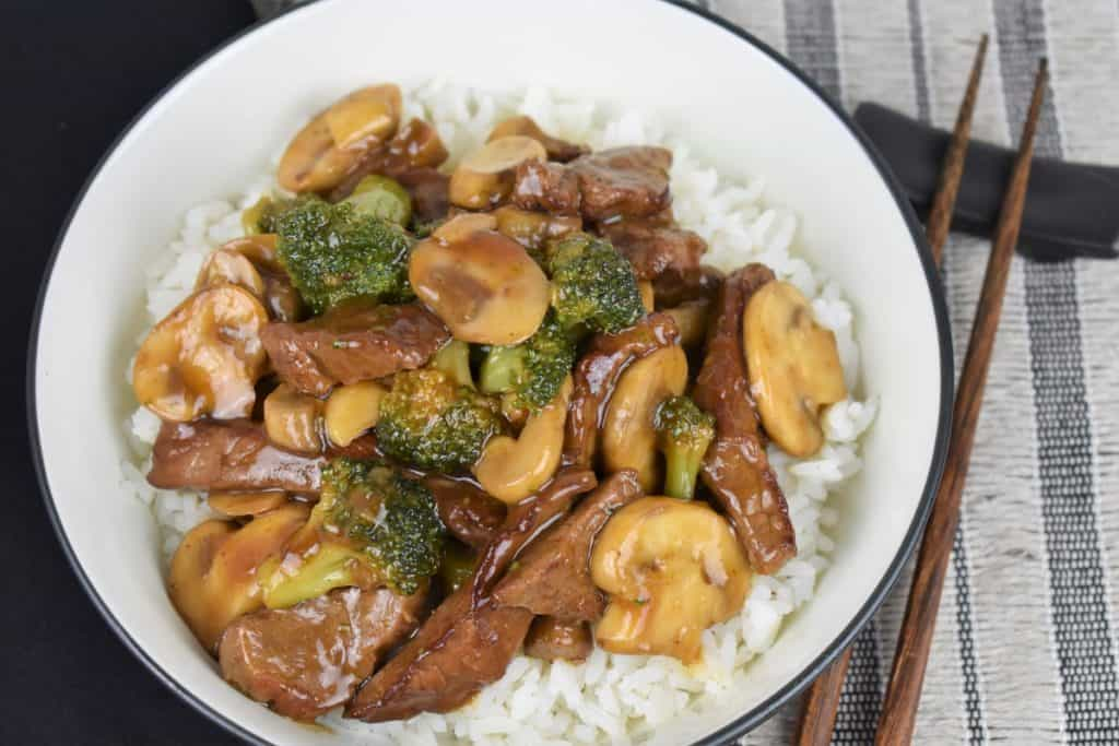 Beef and Broccoli served over white rice in a white bowl