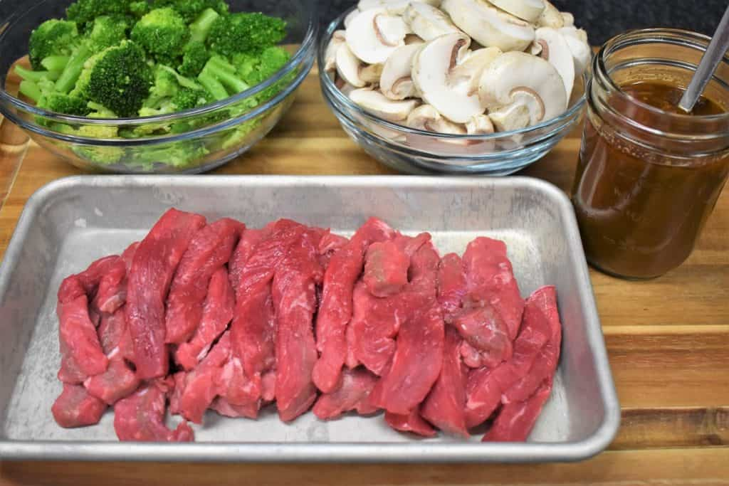Beef and Broccoli Prep, sliced beef, mushrooms, broccoli and Asian sauce displayed on a cutting board prior to cooking