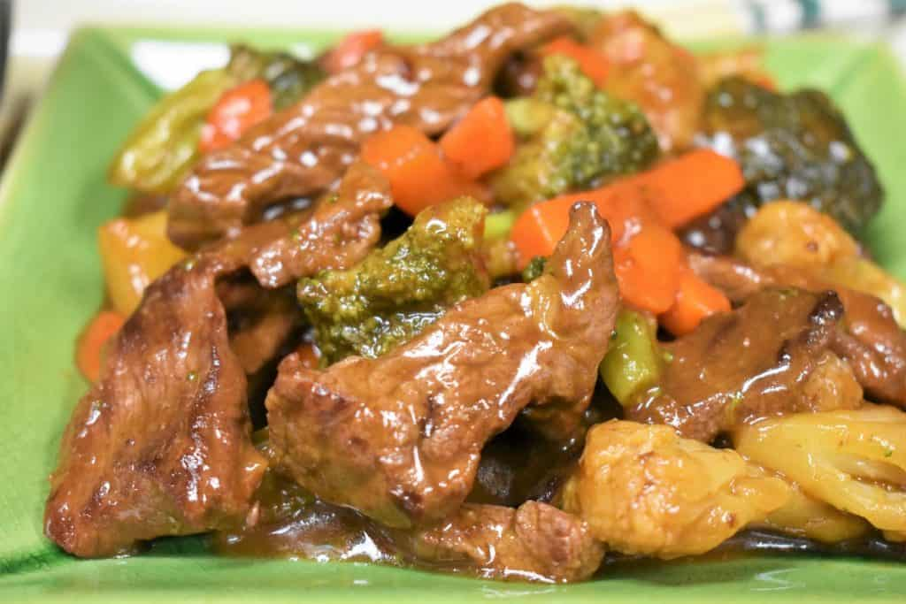 A close up of beef and vegetable stir fry served on a green plate.