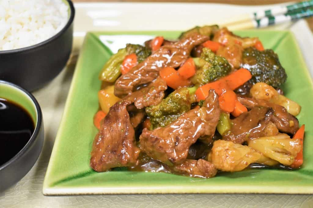Beef and vegetable stir fry served on a green plate with a side of white rice and soy sauce.