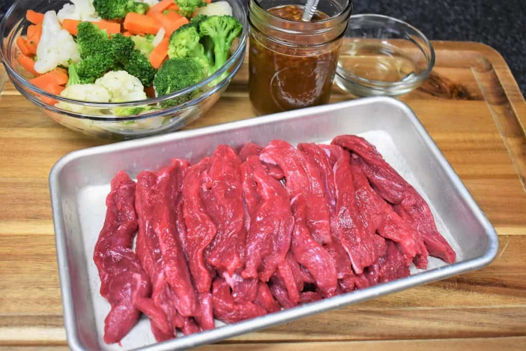 Sliced beef, a bowl of broccoli, cauliflower and carrots and stir fry sauce displayed on a wood cutting board.
