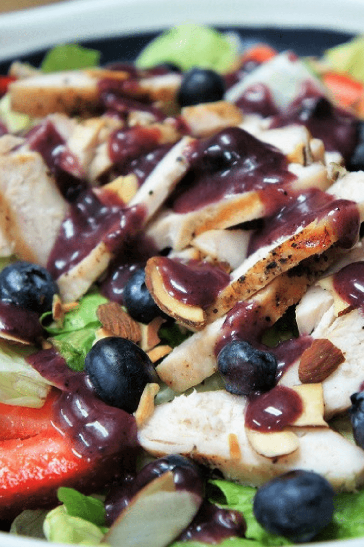 This berry chicken salad is so good you won't mind having a salad for dinner. Simply-seasoned grilled chicken, strawberries, blueberries and toasted almonds all sitting on top of a bed of crisp lettuce. #berrychickensalad #blueberries #salad #summersalads #summertimerecipes