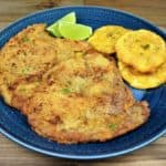 Bistec Empanizado a large, thin breaded and fried steak served with fried green plantains and lime wedges on a blue plate