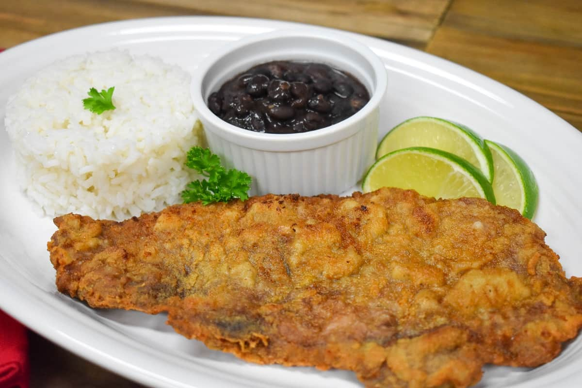 Bistec empanizado served on a large white platter with a side of white rice, black beans and lime wedges.