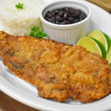 A large thin steak that coated in cracker meal and fried until golden. Served on a large platter with rice, beans and lime wedges.