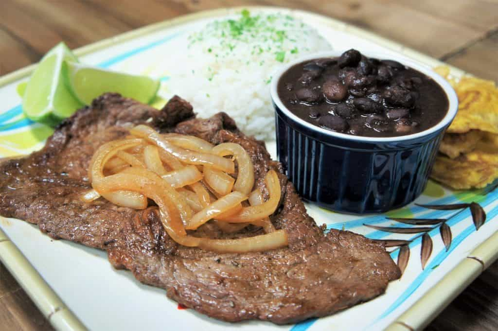 Bistec de Palomilla, thin sirloin steak served with cooked onion, white rice and black beans