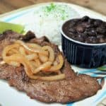 Bistec de Palomilla, thin sirloin steak served with cooked onions, white rice and black beans