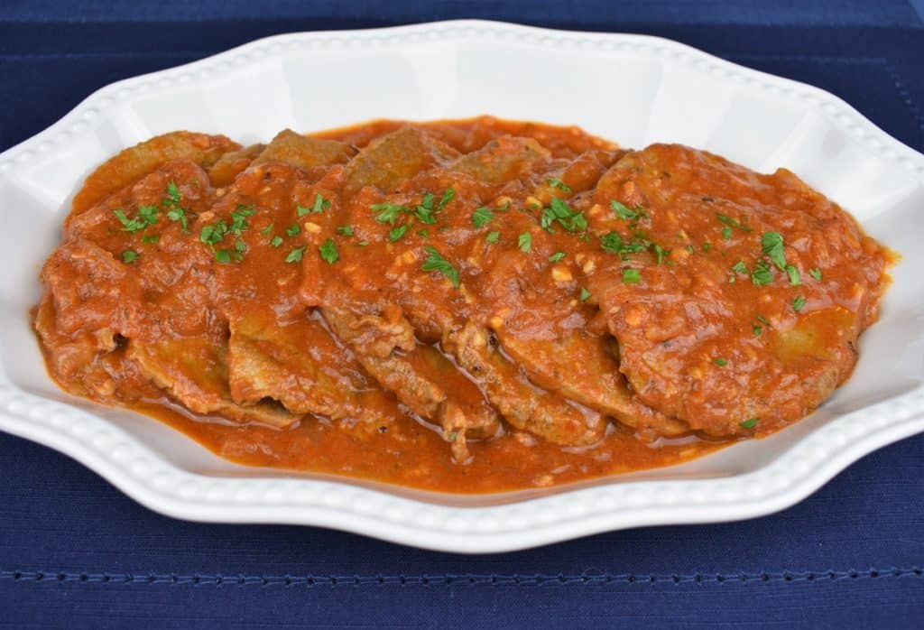 Bistec en Cazuela, thin steaks with a tomato sauce served in a white platter