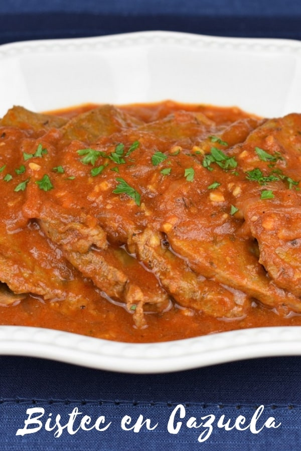 Bistec en cazuela translates to steak in a pot, and that's what it is, kind of. It's thin steaks cooked in a flavorful tomato sauce with garlic and plenty of sliced onions. It's a popular Cuban recipe and really easy to make. Serve it with white rice for a filling, affordable meal, that's also delicious! #bistecencazuela #Cubanfood #cubanrecipes #beef #steakintomatosauce #steak #easyrecipes