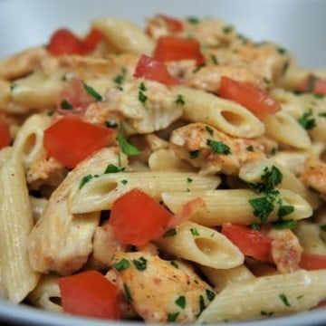 Blackened Chicken & Creamy Pasta with diced tomatoes and garnished with chopped parsley, served in a white bowl