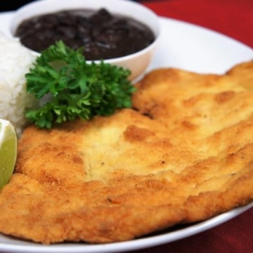 Breaded chicken steak, a thin chicken cutlet that is breaded and fried, served with white rice and black beans on a white plate.
