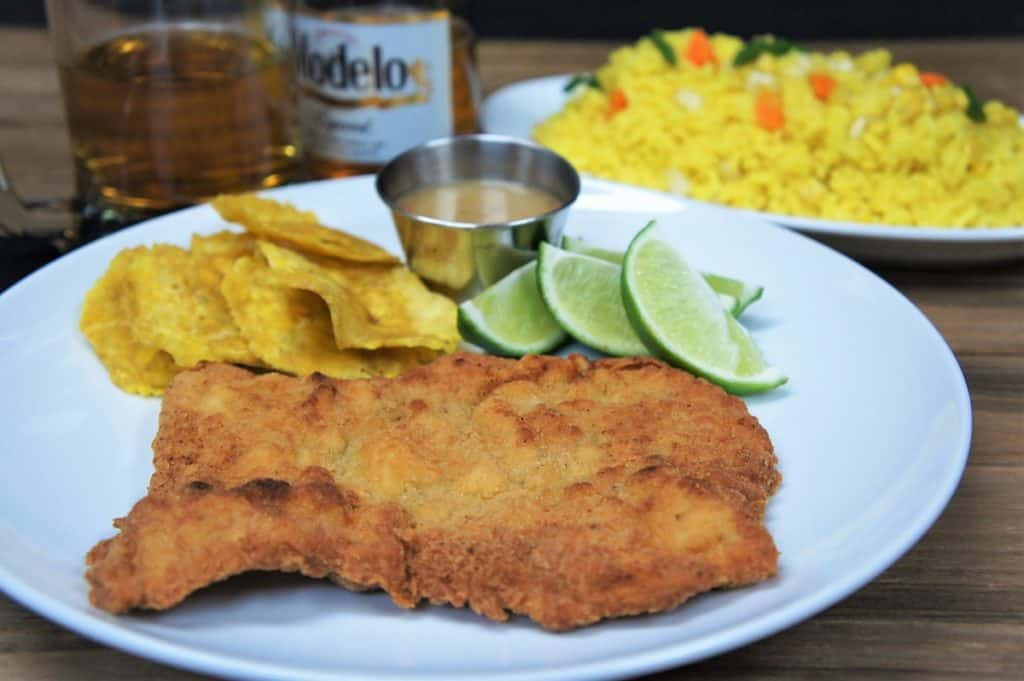 Breaded Pork Steak on a white plate served with plantain chips and lime wedges. A half-filled glass and bottle of beer and yellow rice are in the background.