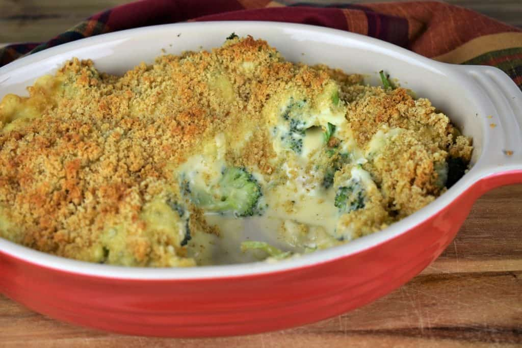 Broccoli Cheese Casserole with some servings missing to expose the broccoli and the creamy sauce