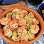 Camarones al Ajillo garlic shrimp in a red clay bowl with olives, cheese and salami displayed in plates on the side