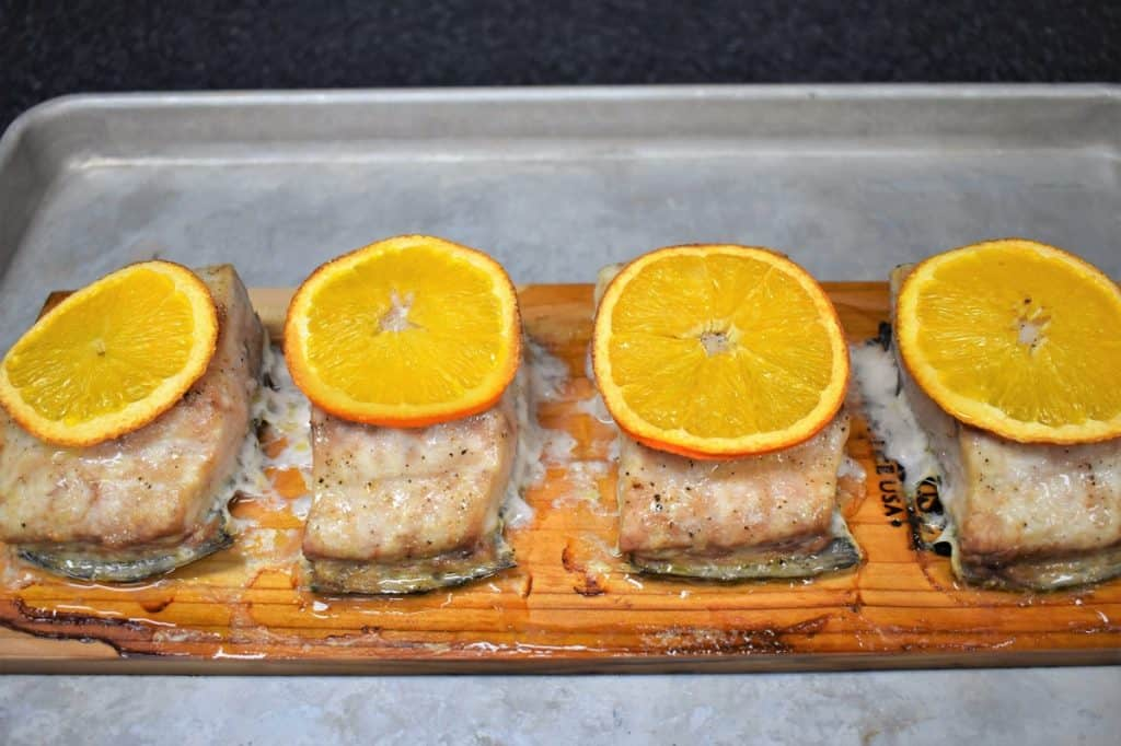 Four pieces of Mahi mahi on a cedar plank, each with a thin orange slice on top.