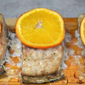 Three pieces of Mahi mahi on a cedar plank with a thin orange slice on top.