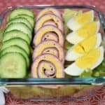 Chef salad with sliced cucumbers, ham, turkey and cheese roll-ups and a quartered hard boiled egg all on top of a bed of lettuce. The salad is in a clear glass, square container.