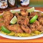 Chicharrones de pollo crispy fried chicken pieces arranged on a white platter with lime wedges and hot sauce bottles in the background.