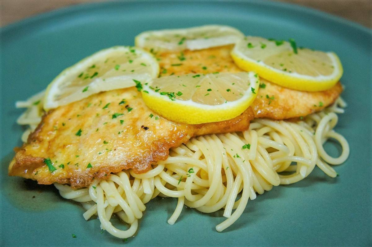 Chicken Francaise on a bed o spaghetti, served on a green plate.