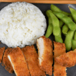 Chicken Katsu thin chicken breast breaded with panko and fried and sliced into strips served on a gray plate with a side of white rice and edamame.