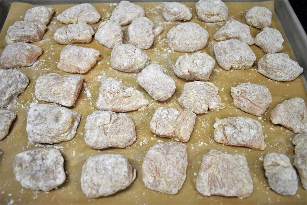 Chicken Nuggets Coated in Flour on a baking sheet lined with parchment paper