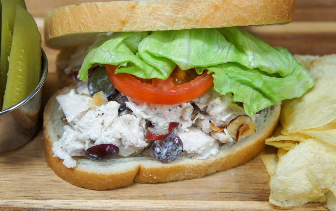 A close up image of the chicken salad on white bread, lettuce and tomato with pickle spears and potato chips on the side.