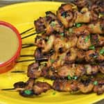 Chicken Satay chicken skewers arranged on a yellow plate, garnished with parsley and served with peanut sauce
