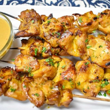 Chicken satay with peanut sauce served on a rectangular, white platter.