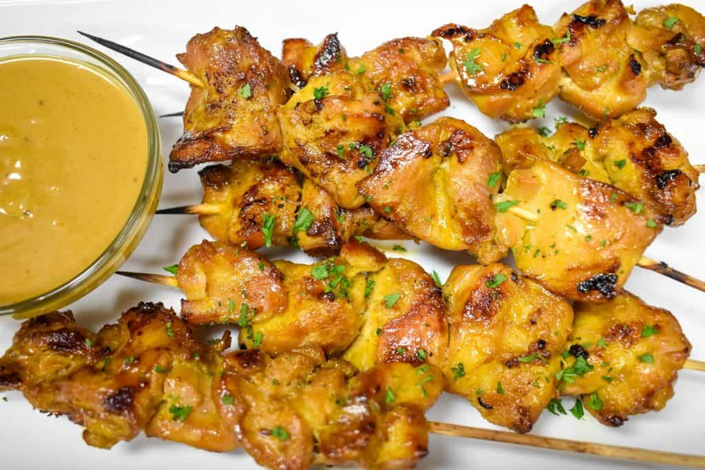 Chicken satay served with peanut sauce on a white platter.