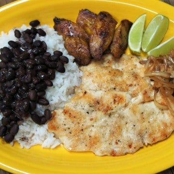 Thin chicken steak fried until golden served with rice, black beans and plantains