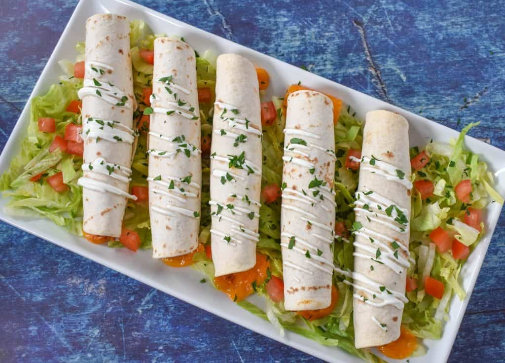 Five taquitos arranged on a white platter on a bed of shredded lettuce with diced tomatoes. They are garnished with a little sour cream and chopped parsley.