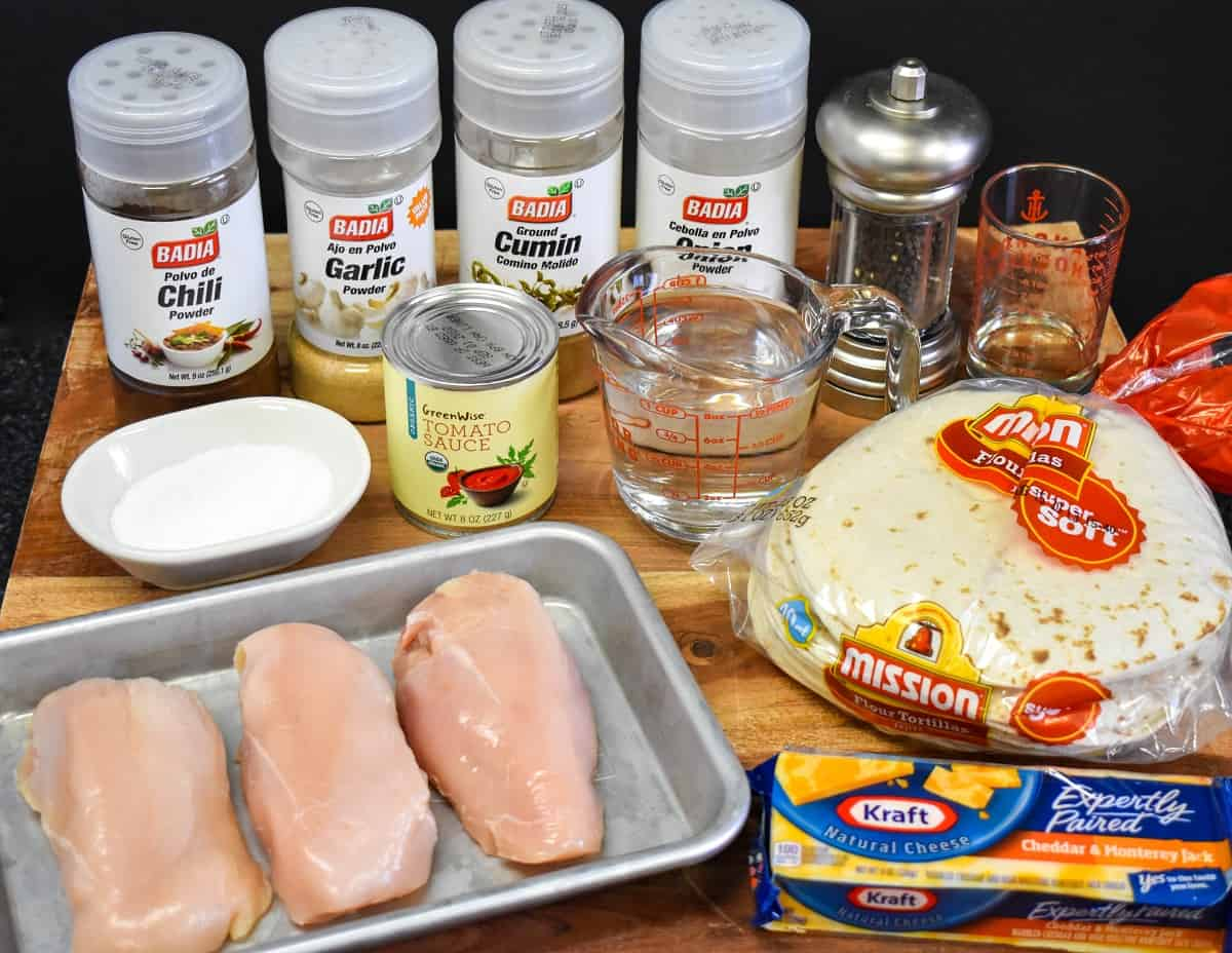 The ingredients for the chicken taquitos arranged on a wood cutting board.