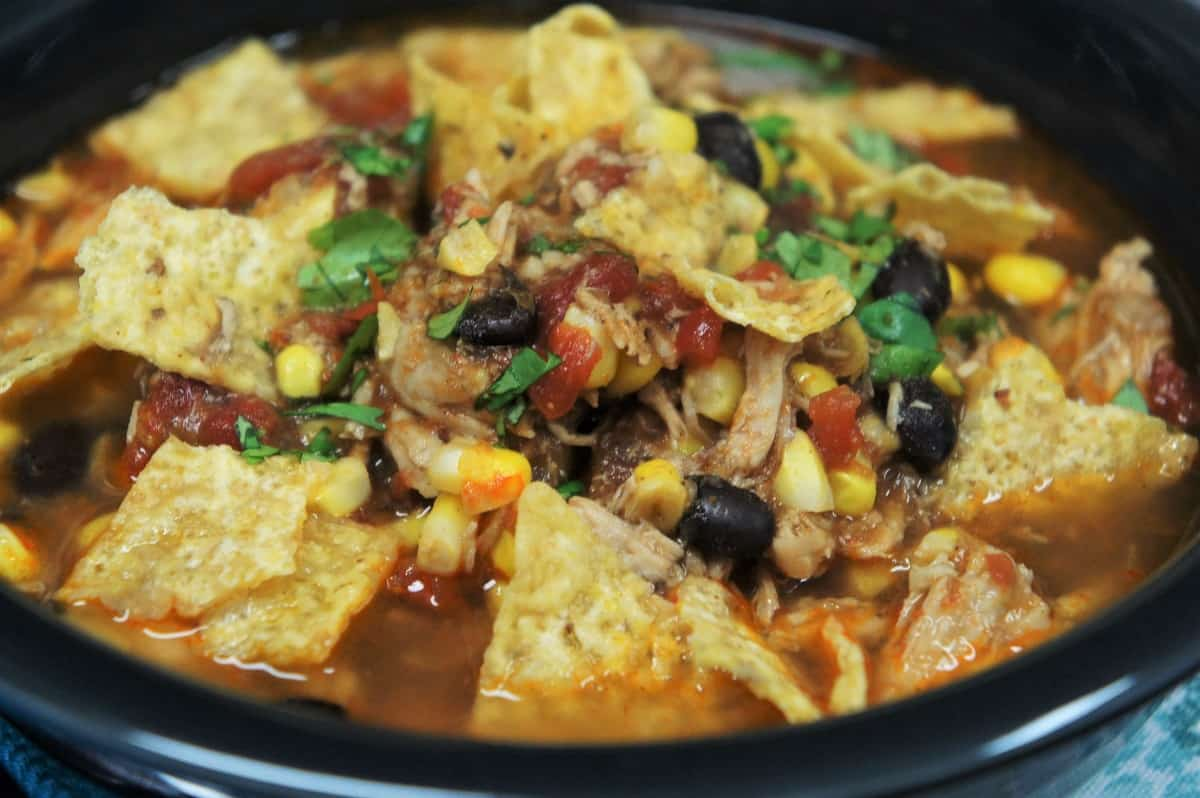 A close up image of the chicken tortilla soup served in a dark gray bowl and garnished with tortilla chips and chopped cilantro.