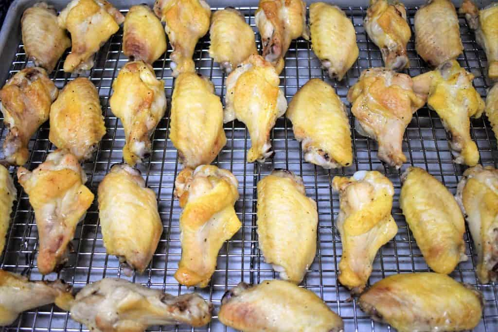 Chicken wings arranged on a sheet pan that's lined with a cooling rack.