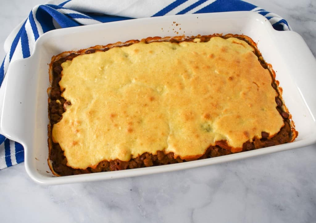 The baked chili cornbread casserole in a white dish with a blue and white striped kitchen towel behind it.