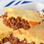 A piece of the chili cornbread casserole held up with a serving spoon over the casserole.