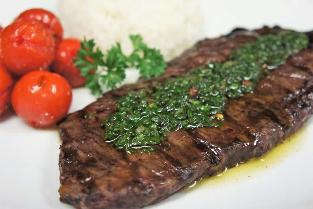 Churrasco & Chimichurri, steak topped with chimichurri sauce served on a white plate with a side of grilled tomatoes and white rice